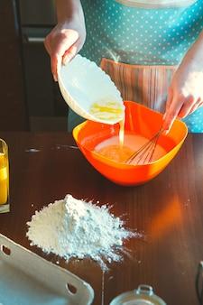 Jovem mulher cozinhando na cozinha, prepara a massa para assar
