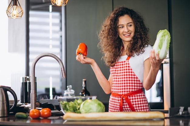 Jovem mulher cozinhando na cozinha
