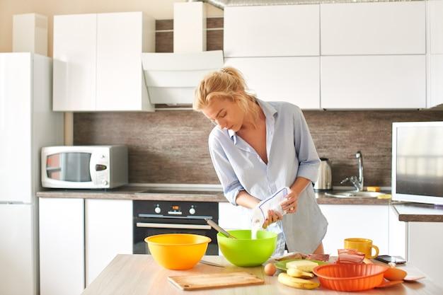 Jovem mulher cozinhando na cozinha.