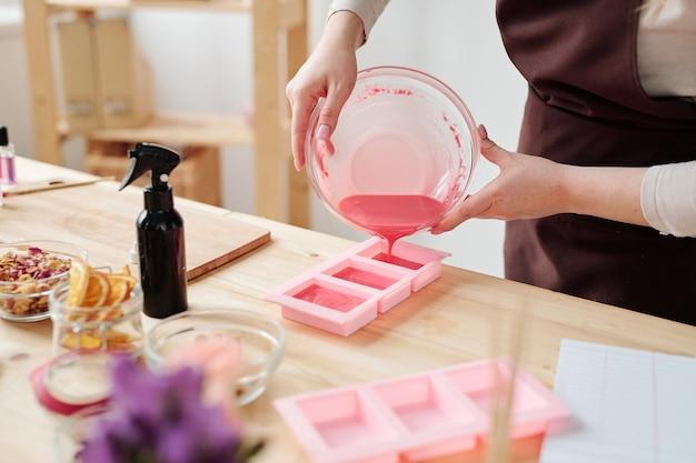 Jovem mulher criativa despejando massa de sabão líquido rosa da tigela em moldes de silicone enquanto fica de pé no local de trabalho