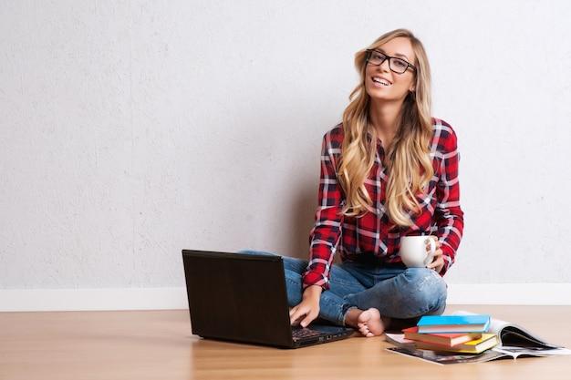 Jovem mulher criativa sentada no chão com laptop./ mulher de blogueira casual