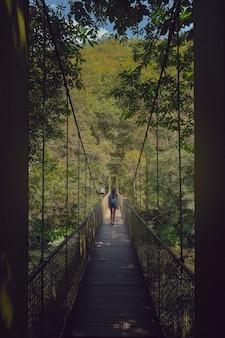 Jovem mulher cruzando uma ponte pênsil na floresta em um dia ensolarado de verão. floresta da galiza. estrada de santiago