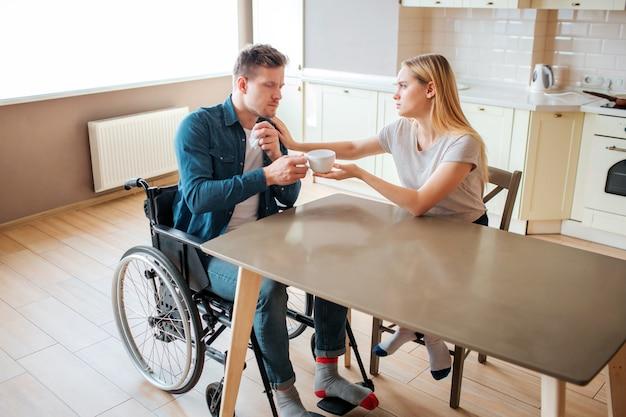 Jovem mulher cuida do homem com necessidades especiais. ele se senta na cadeira de rodas e toma um copo de bebida quente. doente e doente. homem com deficiência e inclusão.