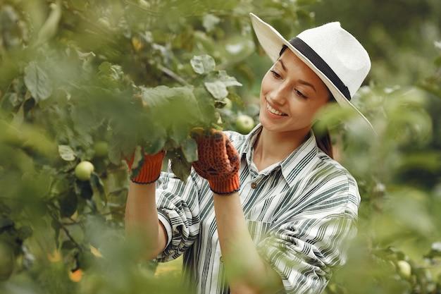Jovem mulher cuidando das plantas. morena com um chapéu e luvas.