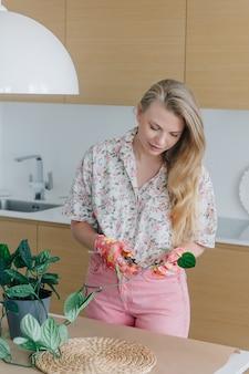 Jovem mulher cuidando de plantas domésticas, poda de galhos com tesouras de podar