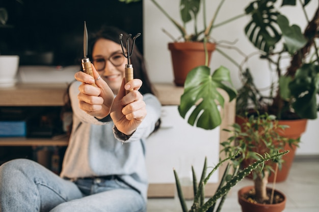 Jovem mulher cultivando plantas em casa