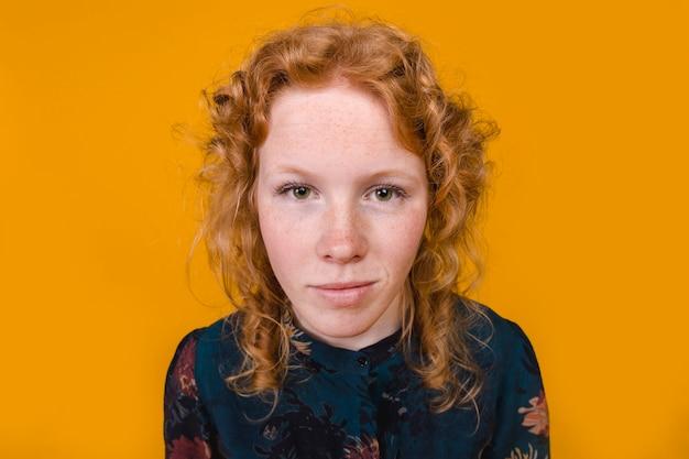 Jovem mulher curly do gengibre que olha a câmera