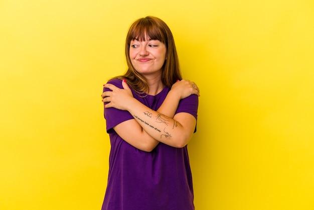 Jovem mulher curvilínea caucasiana isolada em um fundo amarelo abraços, sorrindo despreocupada e feliz.