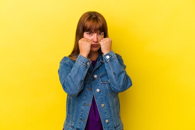 Jovem mulher curvilínea caucasiana, isolada em um fundo amarelo, dando um soco, raiva, lutando devido a uma discussão, boxe.