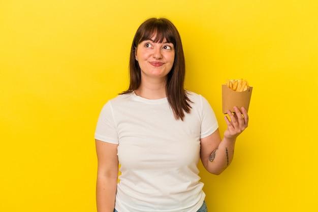 Jovem mulher curvilínea caucasiana segurando batatas fritas isoladas em um fundo amarelo e sonhando em atingir objetivos e propósitos
