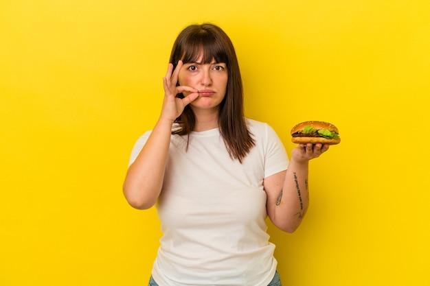Jovem mulher curvilínea caucasiana segurando hambúrguer isolado em um fundo amarelo com os dedos nos lábios, mantendo um segredo.
