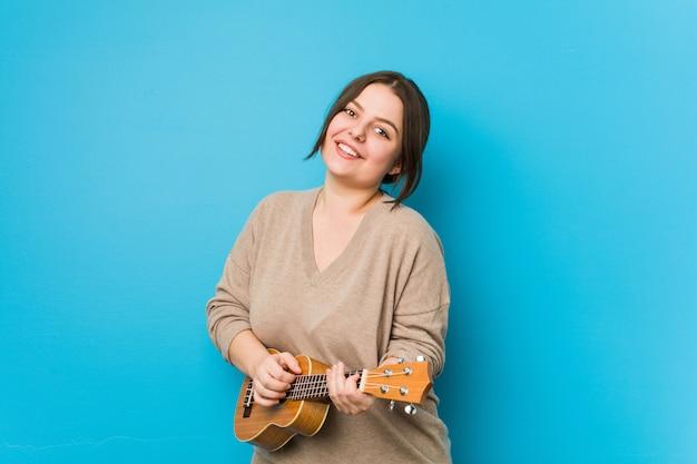 Jovem mulher curvilínea caucasiana tocando ukelele isolado em uma parede azul