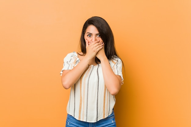 Jovem mulher curvilínea chocada cobrindo a boca com as mãos.