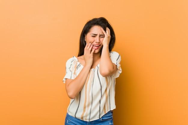Jovem mulher curvilínea choramingando e chorando desconsolada.