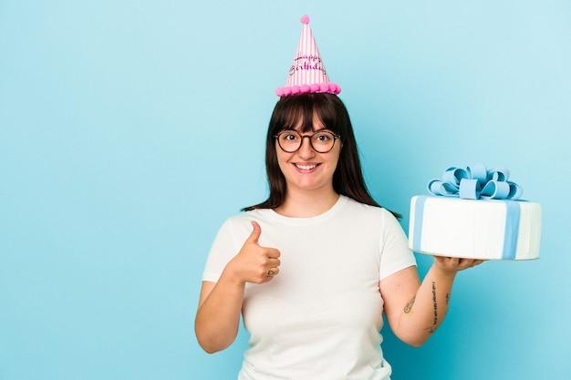 Jovem mulher curvilínea comemorando seu aniversário isolada em um fundo azul, sorrindo e levantando o polegar