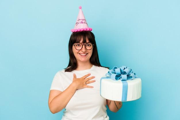 Jovem mulher curvilínea comemorando seu aniversário isolado em fundo azul ri alto, mantendo a mão no peito.