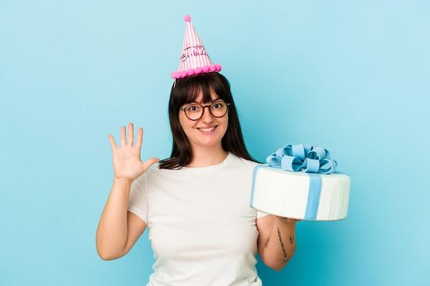 Jovem mulher curvilínea comemorando seu aniversário isolado em fundo azul, sorrindo alegre mostrando o número cinco com os dedos.