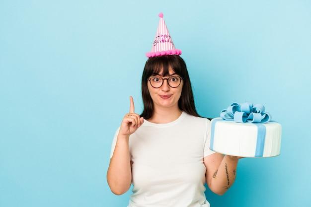 Jovem mulher curvilínea comemorando seu aniversário isolado em um fundo azul, mostrando o número um com o dedo.