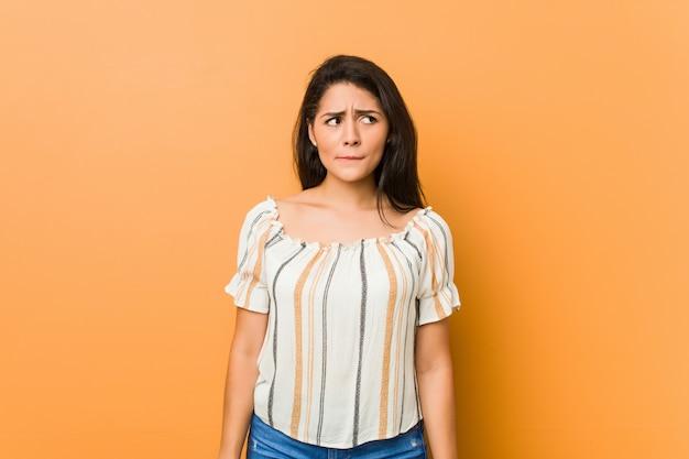 Jovem mulher curvilínea confusa, sente-se duvidosa e insegura.