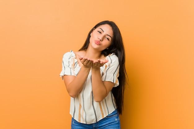 Jovem mulher curvilínea, dobrar os lábios e segurando as palmas das mãos para enviar beijo de ar.