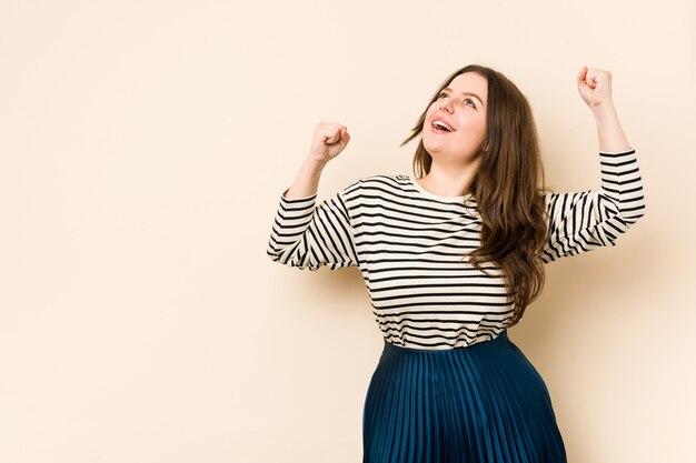 Jovem mulher curvilínea levantando o punho após uma vitória