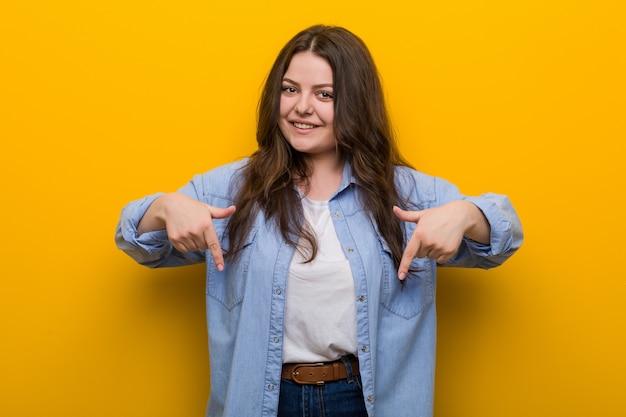 Jovem mulher curvilínea mais tamanho aponta para baixo com os dedos, sentimento positivo.