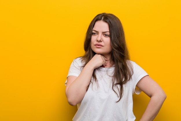 Jovem mulher curvilínea mais tamanho sofre dor na garganta devido a um vírus ou infecção.
