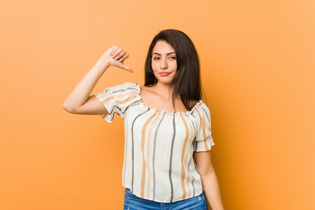 Jovem mulher curvilínea mostrando um gesto de antipatia, polegares para baixo. conceito de desacordo.