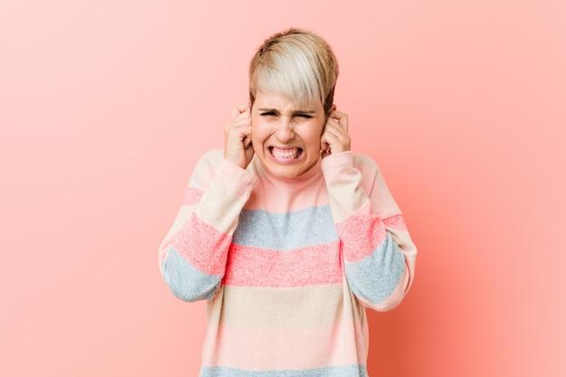 Jovem mulher curvilínea natural, cobrindo os ouvidos com as mãos.