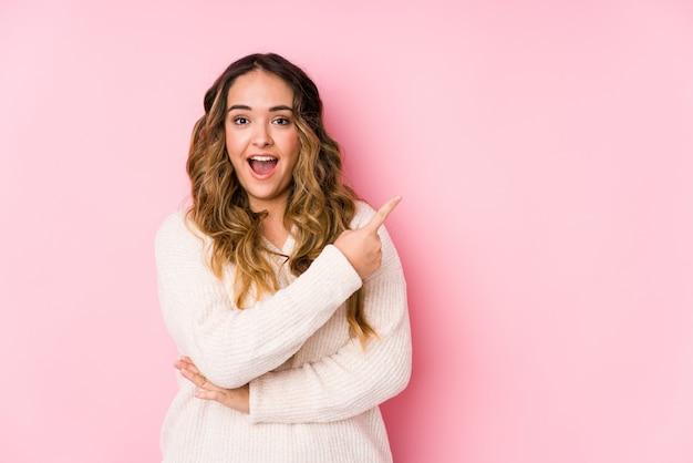 Jovem mulher curvilínea posando em uma parede rosa isolada apontando para o lado