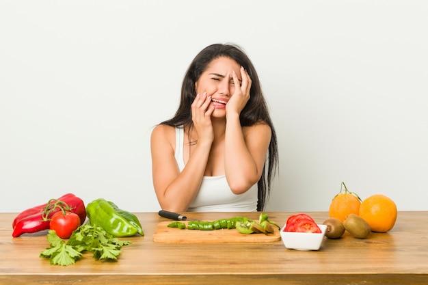 Jovem mulher curvilínea preparando uma refeição saudável, chorando e chorando desconsoladamente.