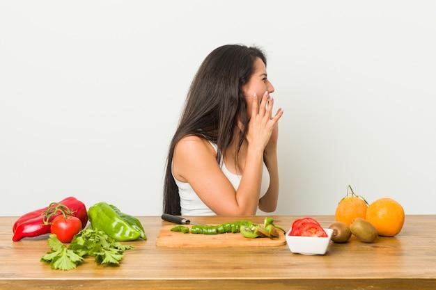 Jovem mulher curvilínea preparando uma refeição saudável grita alto, mantém os olhos abertos e mãos tensas.