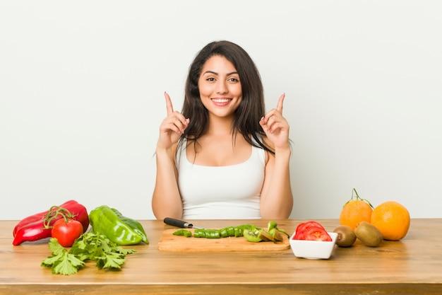 Jovem mulher curvilínea preparando uma refeição saudável indica com os dois dedos da frente