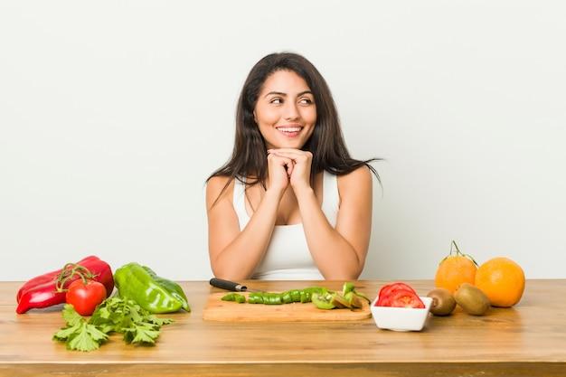 Jovem mulher curvilínea preparando uma refeição saudável mantém as mãos sob o queixo, está olhando alegremente de lado.