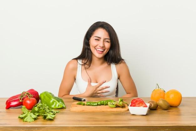 Jovem mulher curvilínea preparando uma refeição saudável ri alegremente e se diverte mantendo as mãos no estômago.