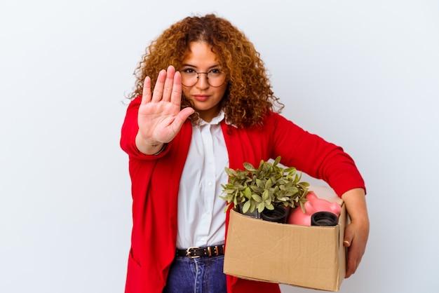 Jovem mulher curvilínea se movendo para uma nova casa, isolada no fundo branco, de pé com a mão estendida, mostrando o sinal de pare, impedindo-o.