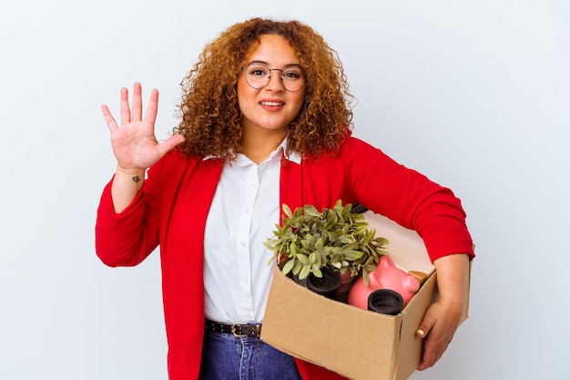 Jovem mulher curvilínea se movendo para uma nova casa, isolada no fundo branco, sorrindo alegre mostrando o número cinco com os dedos.