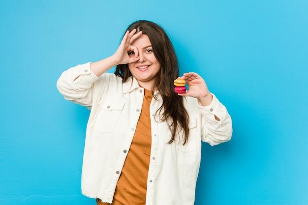 Jovem mulher curvilínea segurando macaroons animado mantendo gesto ok no olho
