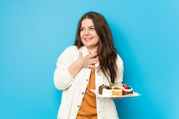 Jovem mulher curvilínea segurando um bolo doce ri alto, mantendo a mão no peito.