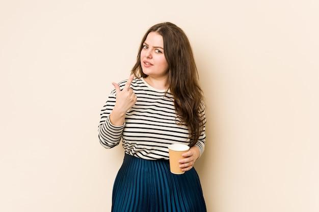 Jovem mulher curvilínea segurando um café apontando com o dedo para você como se fosse um convite para se aproximar.