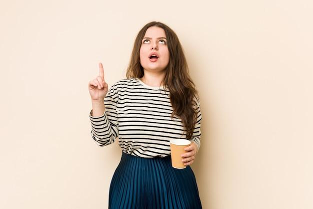 Jovem mulher curvilínea segurando um café apontando para cima com a boca aberta.