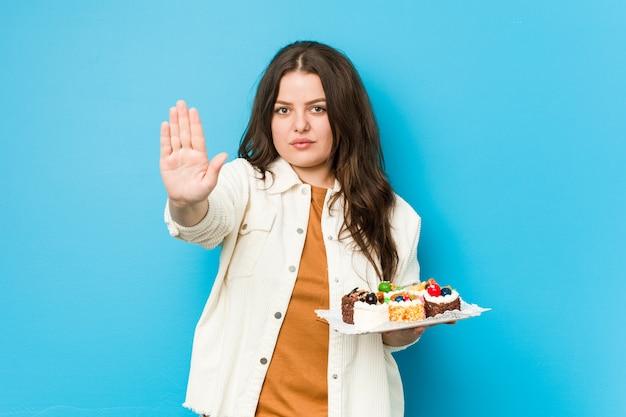 Jovem mulher curvilínea segurando um doce bolos em pé com a mão estendida, mostrando o sinal de stop, impedindo-o.