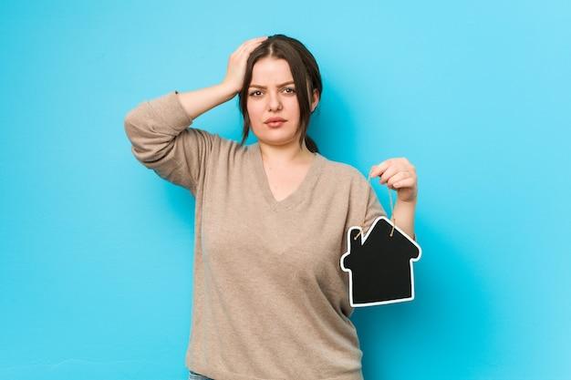 Jovem mulher curvilínea segurando um ícone em casa sendo chocado, ela se lembrou de importante reunião