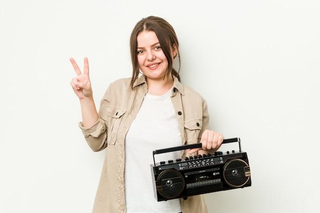 Jovem mulher curvilínea segurando um rádio retrô alegre e despreocupado, mostrando um símbolo de paz com os dedos.