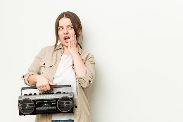 Jovem mulher curvilínea segurando um rádio retrô está dizendo uma notícia secreta sobre a frenagem quente e olhando de lado