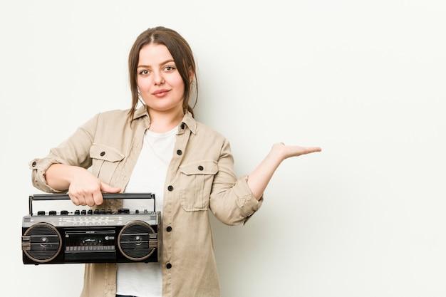 Jovem mulher curvilínea segurando um rádio retrô, mostrando um espaço de cópia na palma da mão e segurando a outra mão na cintura