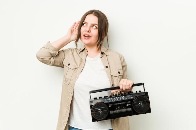Jovem mulher curvilínea segurando um rádio retrô, tentando ouvir uma fofoca.