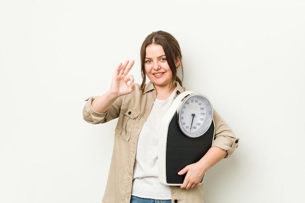 Jovem mulher curvilínea segurando uma balança alegre e confiante mostrando um gesto de ok.