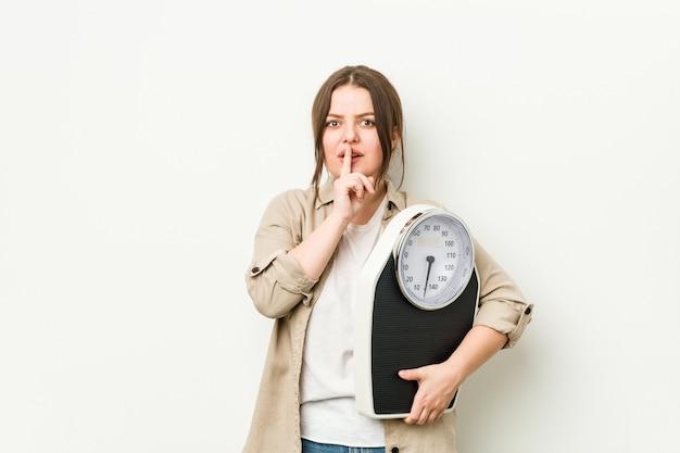 Jovem mulher curvilínea segurando uma balança, mantendo um segredo ou pedindo silêncio.