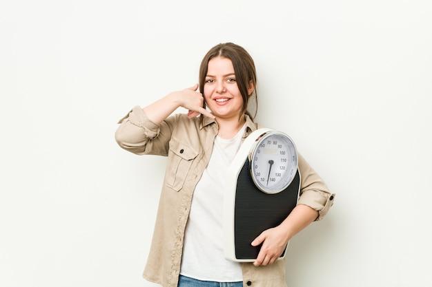 Jovem mulher curvilínea segurando uma balança mostrando um gesto de chamada de celular com os dedos.